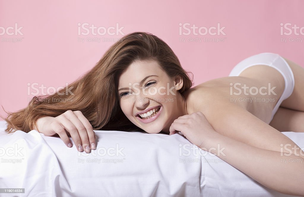 Semi-nude woman laying on bed - Stock image .