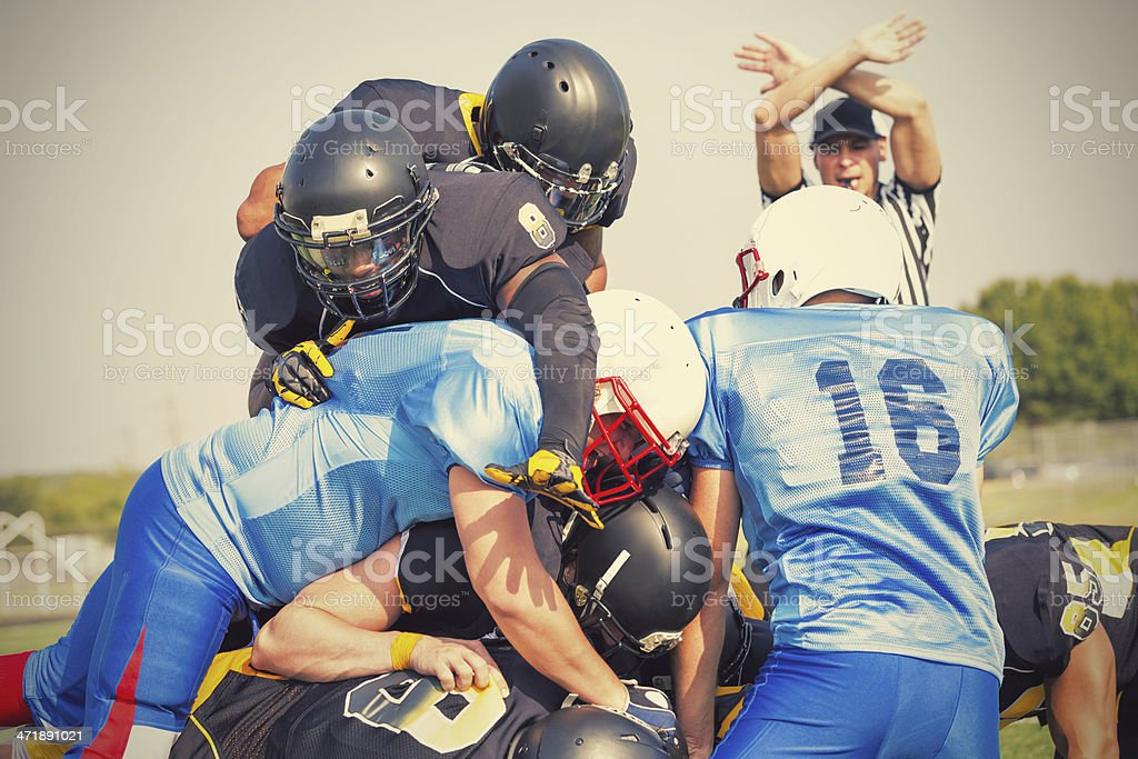 Semi-professional football players tackling opposing team during game royalty-free stock photo
