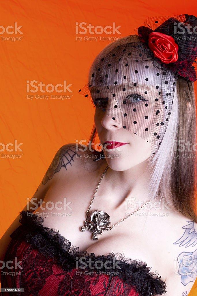 Semi-profile of veiled woman on orange. royalty-free stock photo