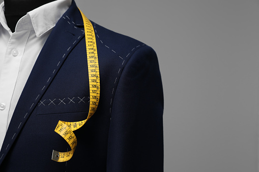 Semi-ready jacket with tailor's measuring tape on mannequin against grey background, closeup. Space for text