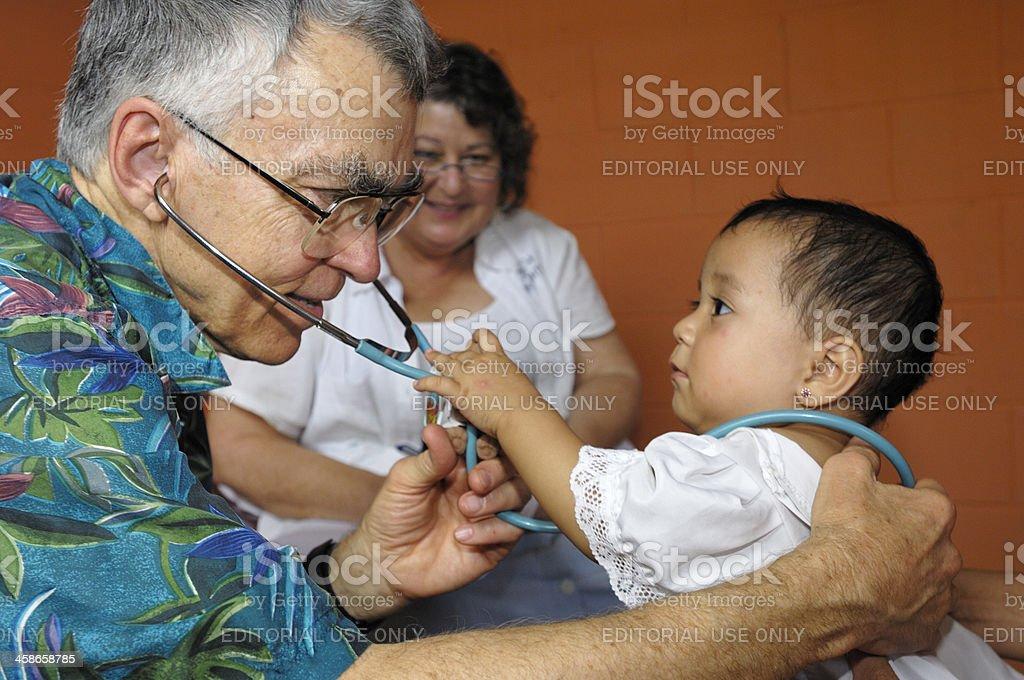 Semi-retirado pediatra examina bebé niña. - foto de stock