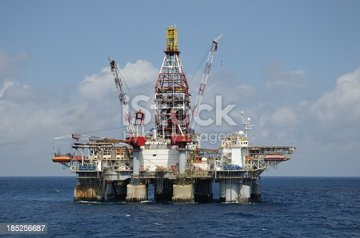 A  free floating dynamically positioned semi-submersible deep water oil drilling platform on location in blue water. An off shore oil rig.