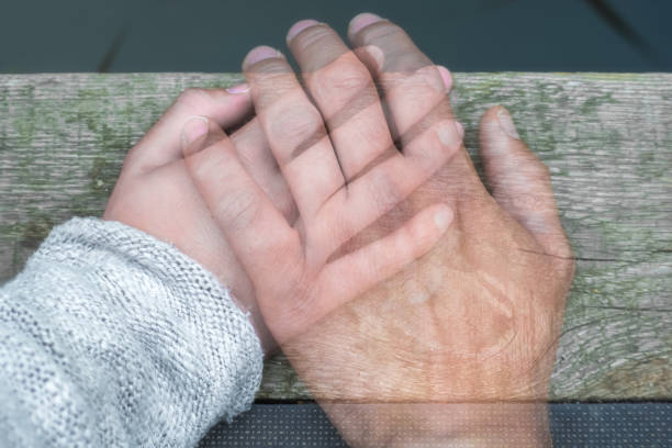 Semi-transparent man's hand on a woman's hand as a sign of farewell by separation or death loss dead stock pictures, royalty-free photos & images