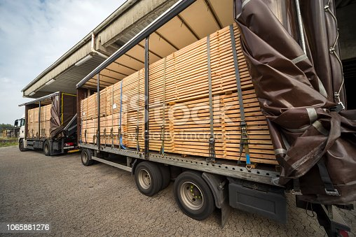 Semi-truck and trailer with stacked wooden planks in warehouse for wood and timber construction material. Blue sky, outdoors.