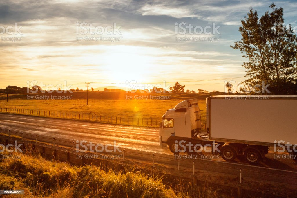 Semi-truck at sunset traveling through the rural landscape of New Zealand stock photo