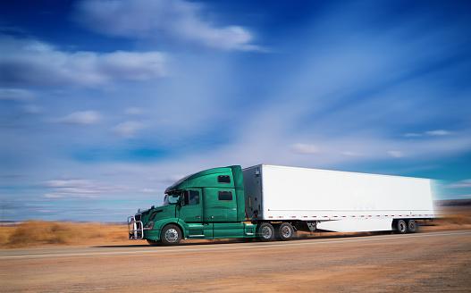 Semi-truck driving on a rural road in Arizona USA