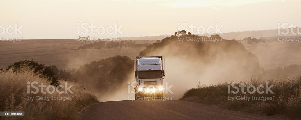 Semi-truck driving on dirt road stock photo