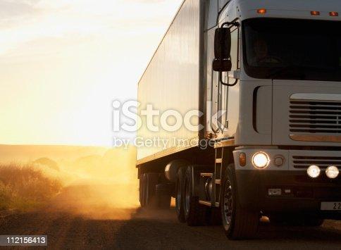 istock Semi-truck driving on dusty dirt road 112156413
