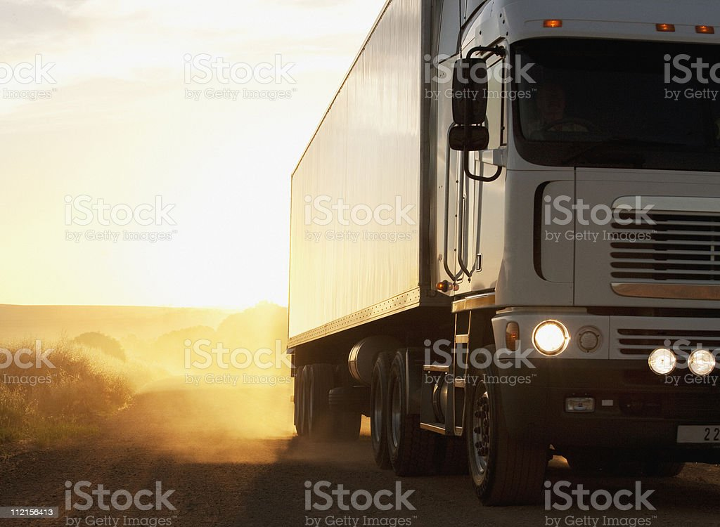 Semi-truck driving on dusty dirt road stock photo
