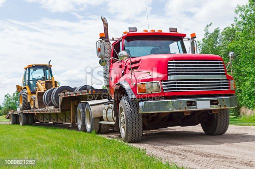 A semi-truck is hauling a tractor with a backhoe, loader and tires. It is parked on a country gravel road along green grass and trees