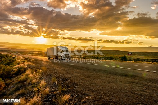 Beautiful sunset behind a semi-truck heading down the interstate in Utah desert.