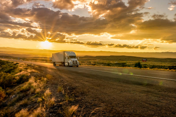 semi-truck on an interstate highway at dusk with cloudscape - transport truck tyres foto e immagini stock