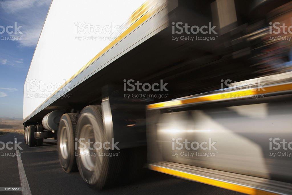 Semi-truck speeding on remote road stock photo