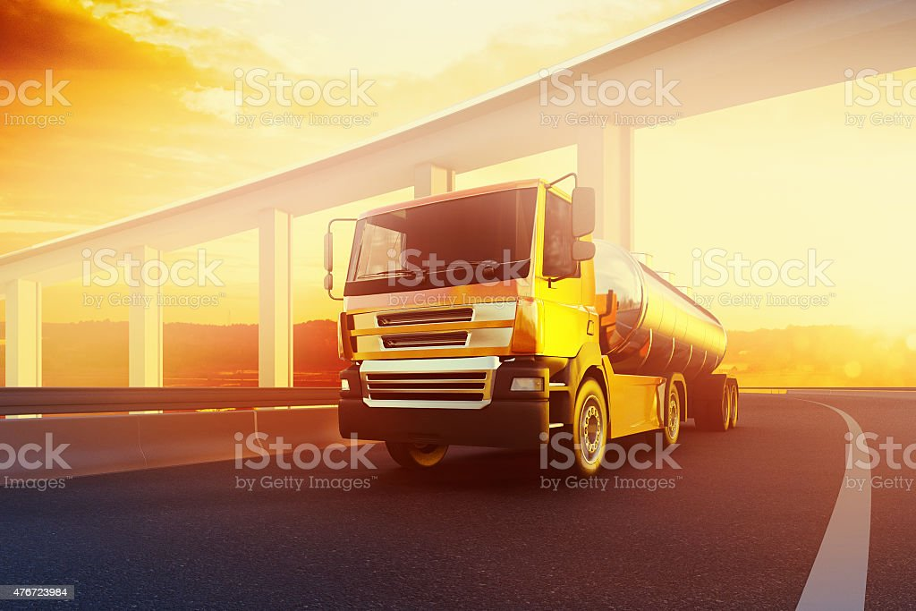 Semi-truck with oil cistern on asphalt road highway at sunset stock photo