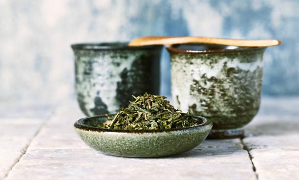 Sencha green Tea Leaves and Japanese Ceramic Tea Cups stock photo