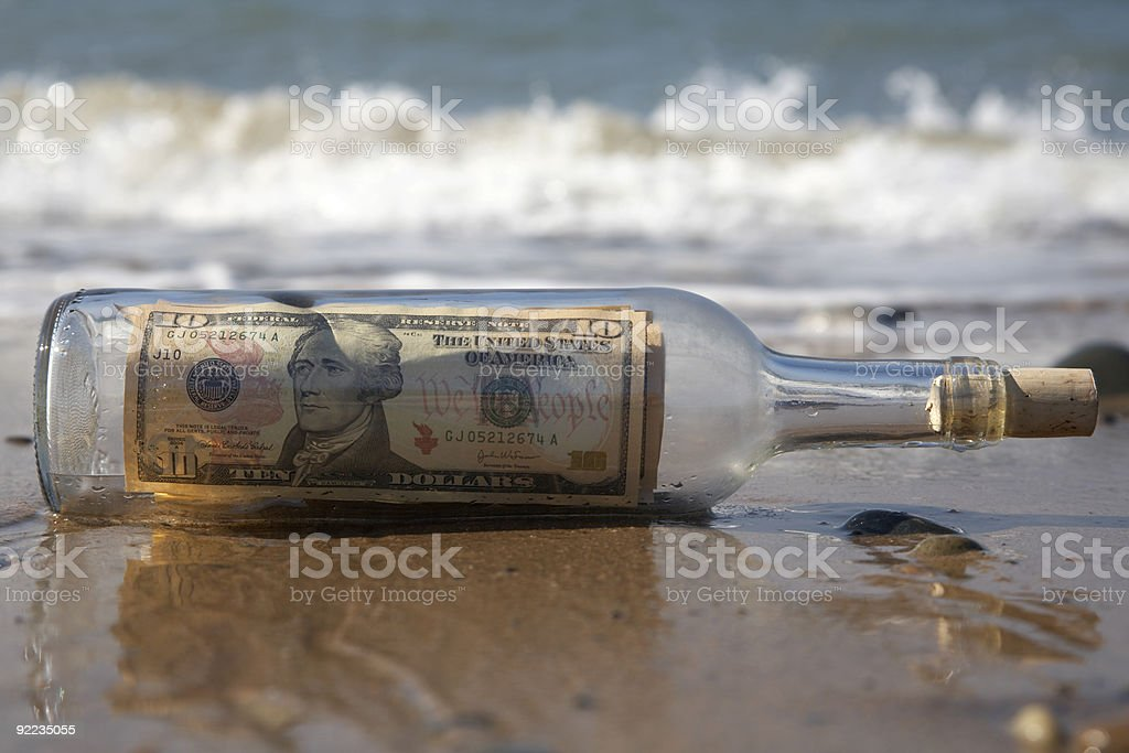 send or transfer money - message in bottle on beach stock photo