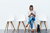 Full length studio shot of an attractive young businesswoman sitting down on a chair and using her cellphone