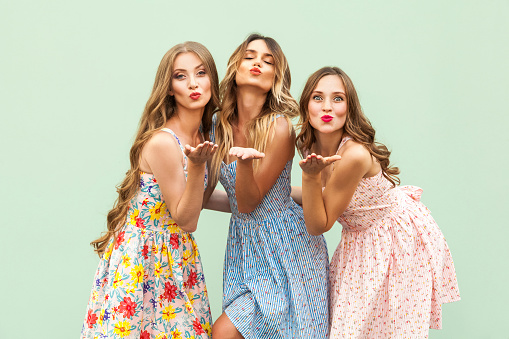 istock Sending air kiss. Three best friends posing in studio, wearing summer style dress against green background. 850137602