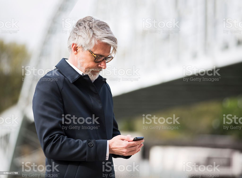 Sending an sms with a smart phone on the street. stock photo