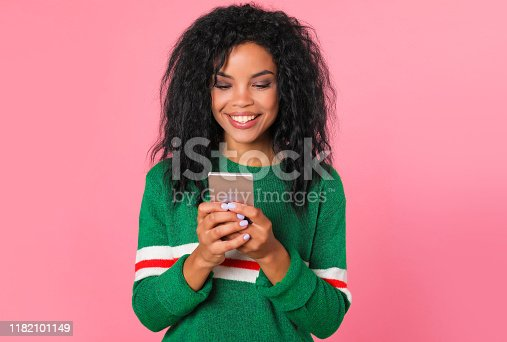 909457386istockphoto Sending e-mails. African American girl in a green sweater with white and red stripes is looking at the screen of her smartphone, which she is holding in her hands, while smiling sincerely. 1182101149