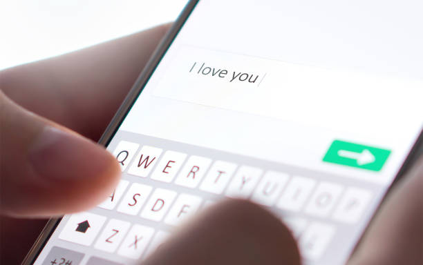 Sending I love you text message with mobile phone. Online dating, texting or catfishing concept. Romance fraud, scam or deceit with smartphone. Man writing comment. stock photo