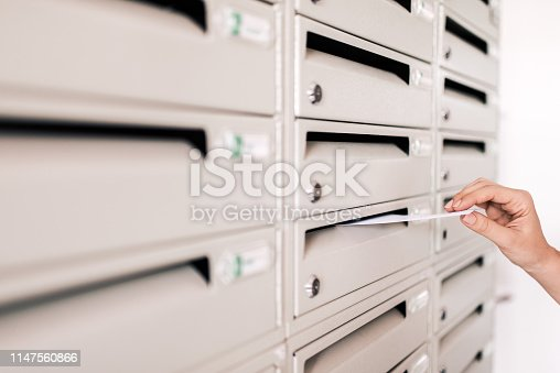 istock Sending mail. Putting letters in apartment building mailbox, close-up. 1147560866