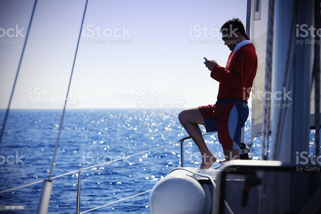 Sending SMS from sailboat royalty-free stock photo