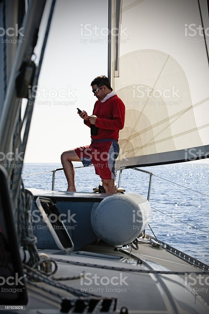 Sending SMS from sailboat stock photo