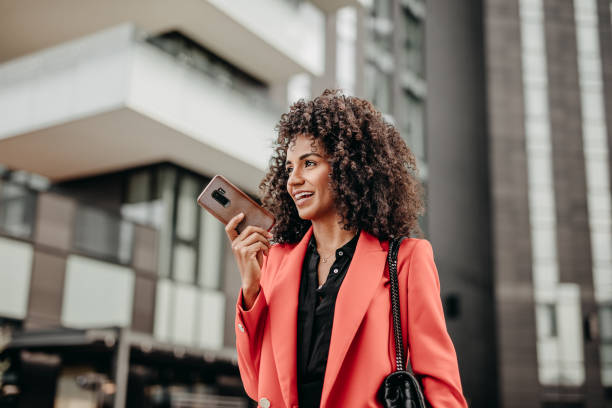 Sending voice messages on the move Beautiful businesswoman in read coat on her way to work place speech recognition stock pictures, royalty-free photos & images