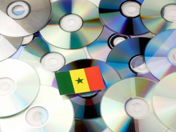 senegal fahne auf cd- und dvd-stapel, isoliert auf weiss - senegal news stock-fotos und bilder
