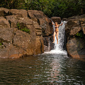 Cool tropical vacations. Mature woman jumping into the water from a waterfall.