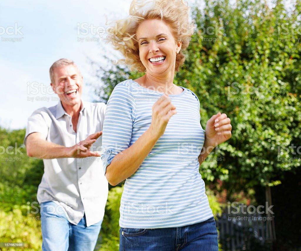 Senior active man running behind mature woman royalty-free stock photo