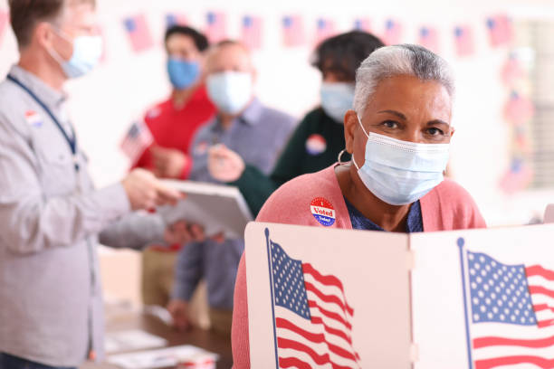 Senior adult, African descent woman votes in USA election wearing mask. stock photo