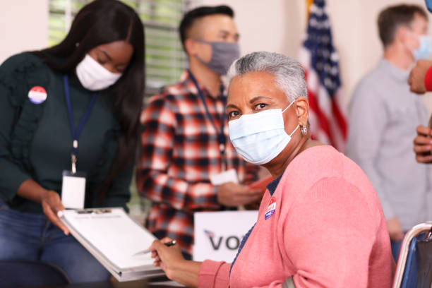 senior adult, african descent woman votes in usa election wearing mask. - polling place stock pictures, royalty-free photos & images