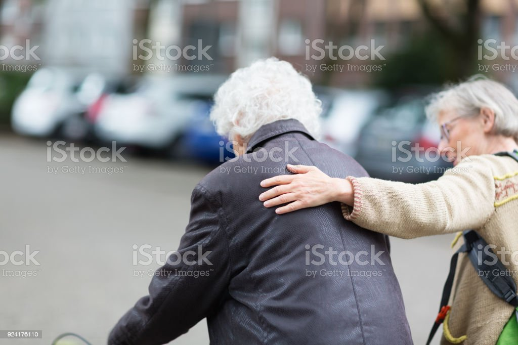 senior adult and mature cargiver, supporting with her hand stock photo