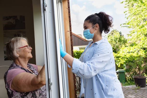 senior adult and young woman meeting during COVID-19 pandemic separated by the window stock photo
