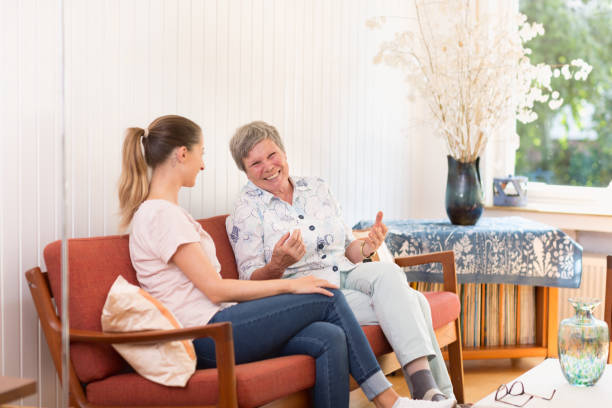 Senior Adult and young woman talking, sitting on sofa in liivingroom stock photo
