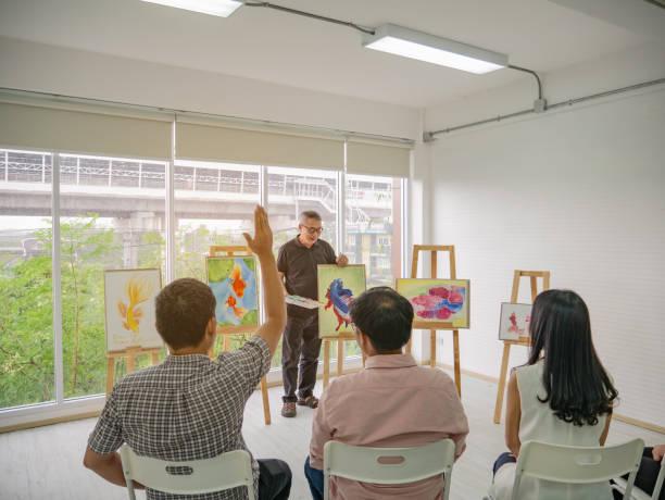 älteren erwachsenen künstler lehrer unterricht seines schülers hand aufmachungen und frage im klassenzimmer - senior bilder wasser stock-fotos und bilder