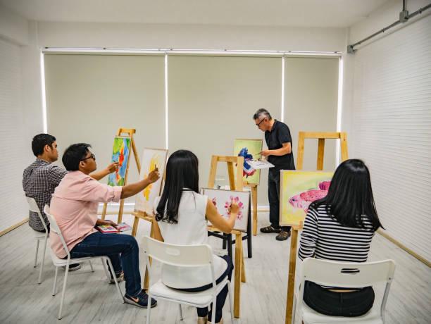 älteren erwachsenen künstler lehrer unterricht im klassenzimmer - senior bilder wasser stock-fotos und bilder