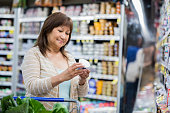 Senior adult Asian female is shopping at a grocery store. She is reading nutrition facts on the label. She has brown hair and is shopping alone.