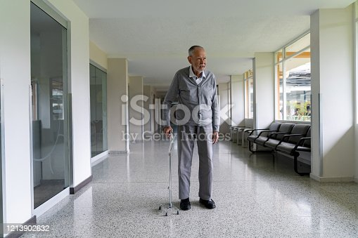 Senior adult at the hospital walking with a cane - geriatric medicine concepts