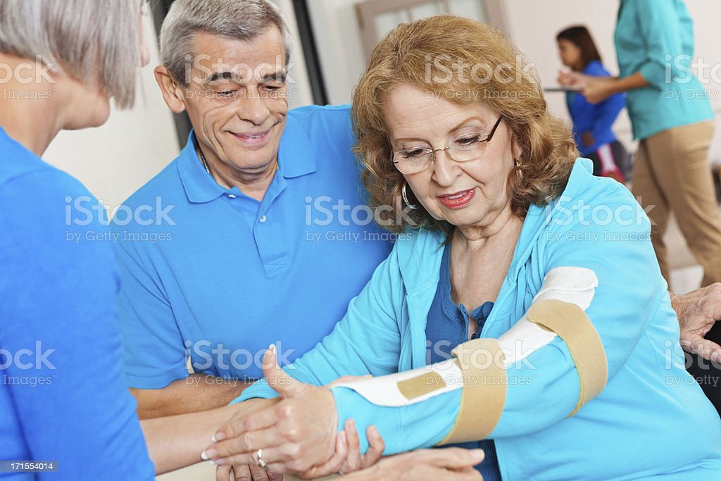 Senior adult being treated with arm brace at clinic stock photo