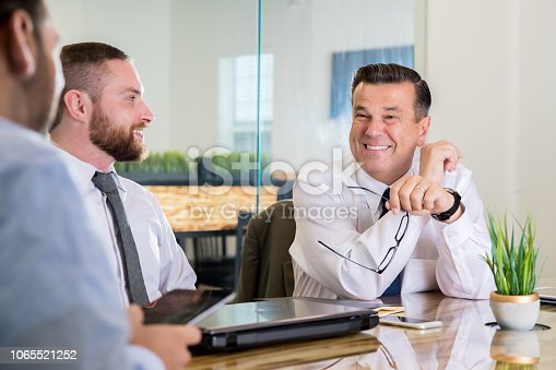 istock Senior adult Caucasian man in business meeting with mid adult men 1065521252