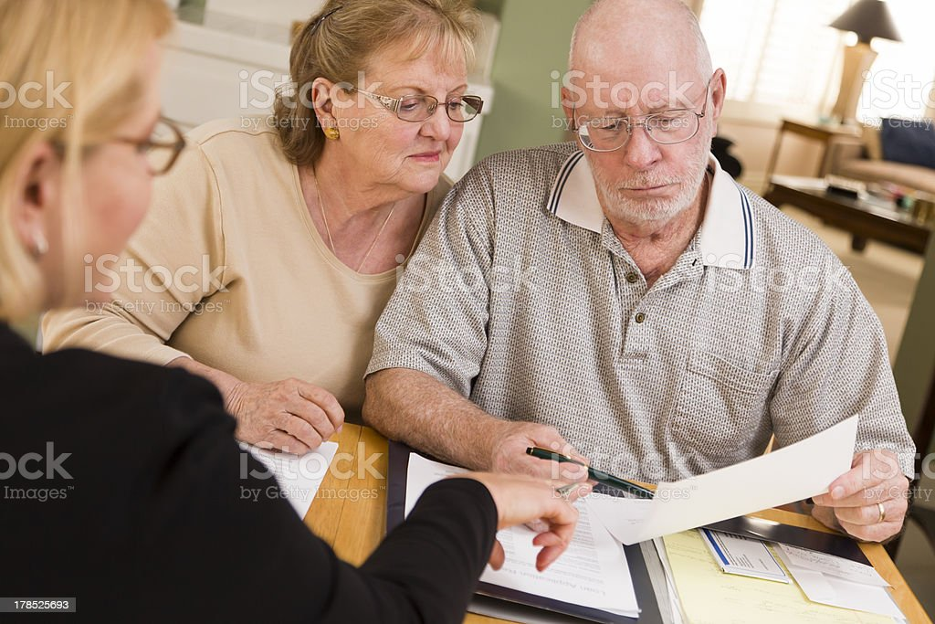 Senior Adult Couple Going Over Papers in Home with Agent stock photo