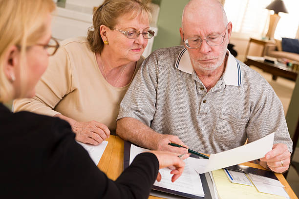 Senior Adult Couple Going Over Papers in Home with Agent Senior Adult Couple Going Over Papers in Their Home with Agent. medicare stock pictures, royalty-free photos & images