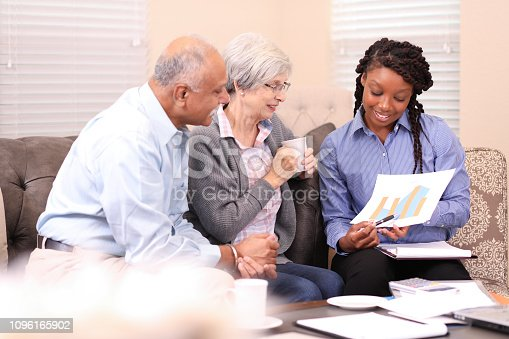 Senior adult couple meets with financial advisor, home consultant, insurance agent, final expense advisor, or realtor at home.  African, Indian, Caucasian ethnicities.