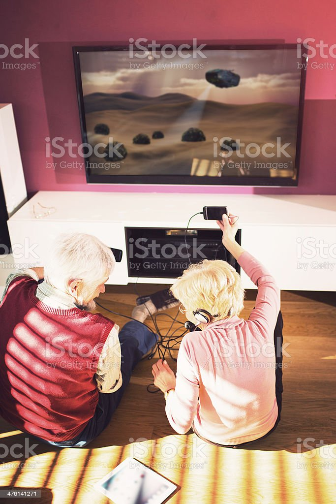 Senior adult couple playing video games in living room royalty-free stock photo