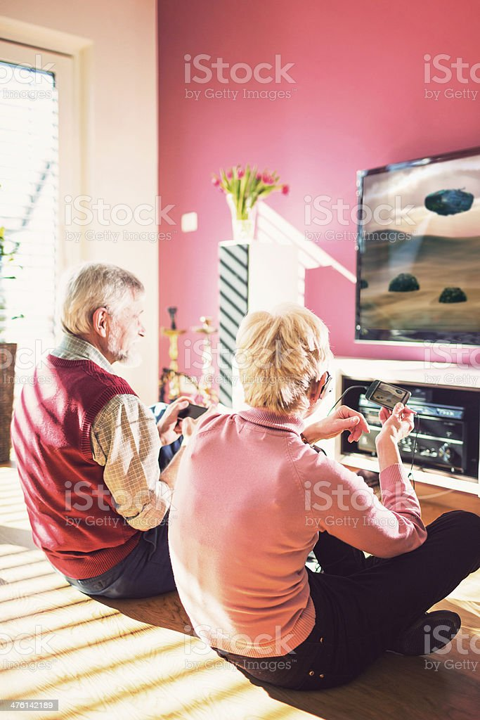 Senior Adult Couple Playing Video Games In Living Room stock photo ...