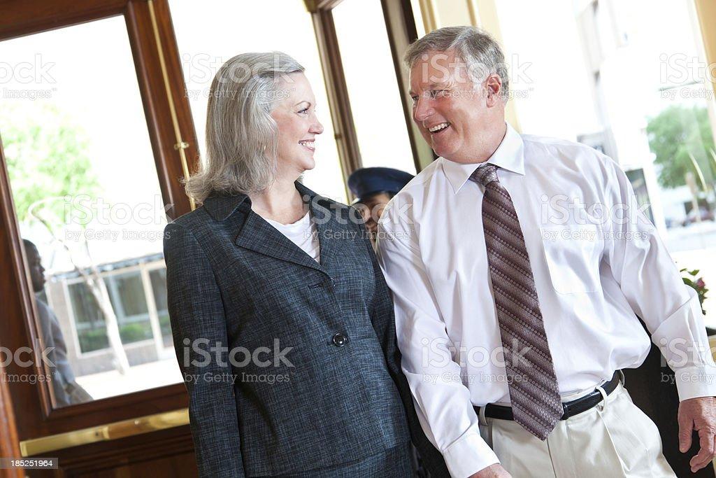 Senior adult couple walking into hotel together royalty-free stock photo