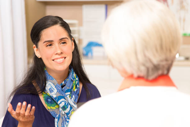 Senior adult female doctor, therapist and patient in office, clinic. stock photo